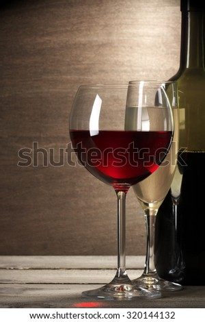 Glasses of red and white wine and bottle on rustic wooden background.