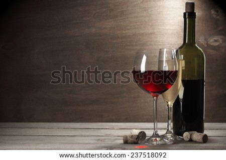 Glasses of red and white wine and bottle with corks on rustic wooden background with copy space. - stock photo