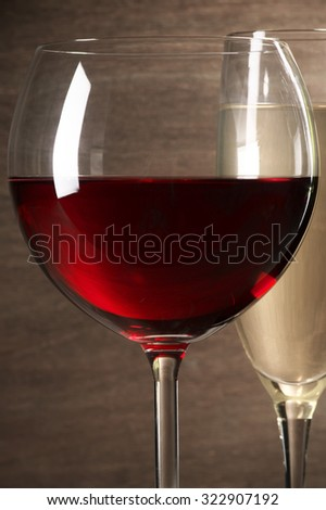 Glasses of red and white wine close-up on wooden background. Shallow DOF. - stock photo