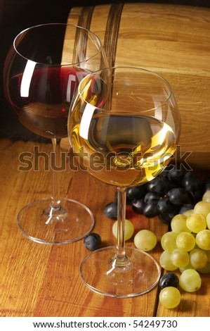 Glasses of red and white wine, grape and souvenir barrel on wooden surface. - stock photo
