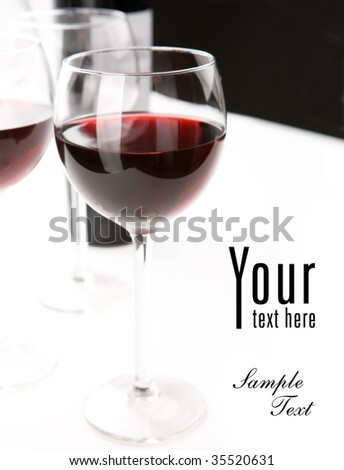 Glasses of red whine on white table cloth. Space for text isolated on white. Black background.