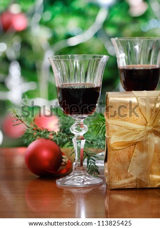 Glasses of red wine and Christmas decorations in front of Christmas tree for the holidays