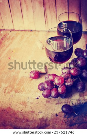 Glasses of red wine, grape and corks on wooden table - stock photo