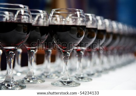 Glasses of red  wine in a row on table - stock photo