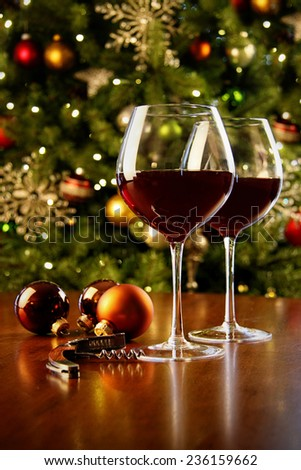 Glasses of red wine on table with Christmas tree in background  - stock photo