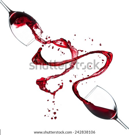 Glasses of red wine splashing out, isolated on white background - stock photo