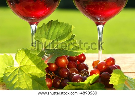 Glasses of  red wine with grapes on a table