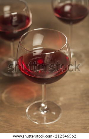 Glasses of red wine with white wooden background