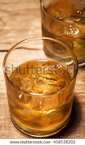 Glasses of scotch on wooden vintage background