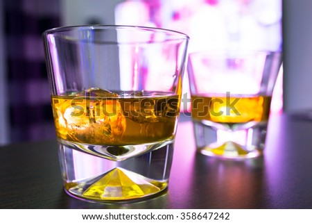 Glasses of scotch whiskey on ice at the tv - stock photo