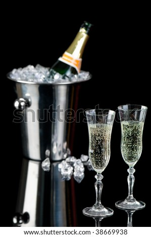 Glasses of sparkling champagne with bottle in ice bucket in background - stock photo
