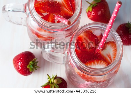 Glasses of strawberry summer water. Cold fruit drinks on white and blue wooden background. Refreshment drinks concept.