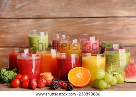 Glasses of tasty fresh juice, on wooden table. - stock photo