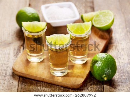 glasses of tequila with lime on wooden table - stock photo