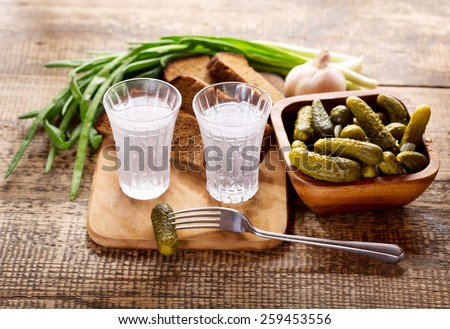glasses of vodka with various snack on wooden table