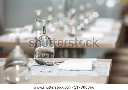 Glasses of water lined up on luxury table setting for dining, selective focus with bokeh background - stock photo