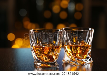 Glasses of whiskey on bar background - stock photo