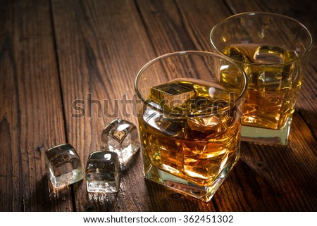Glasses of whiskey with ice on wooden table - stock photo