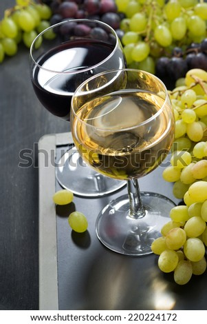 glasses of white and red wine and grapes on a blackboard, close-up - stock photo