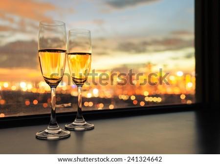 Glasses of white wine against sunset  - stock photo