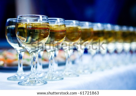 Glasses of white wine in a row on table - stock photo