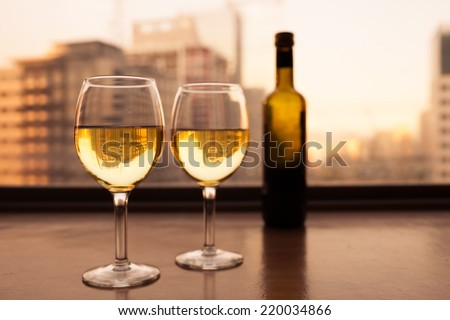 Glasses of white wine with city view. Fine dining concept. - stock photo