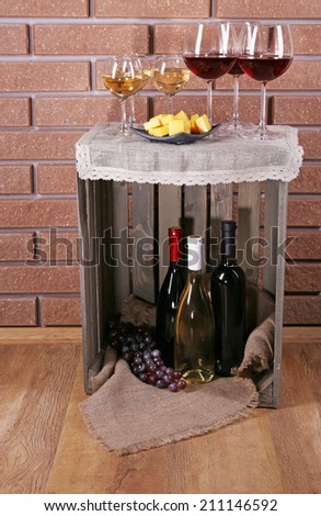 Glasses of wine and cheese on box on brick wall background - stock photo