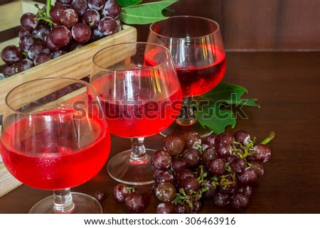 Glasses of wine and  grapes in wooden crate on wooden background