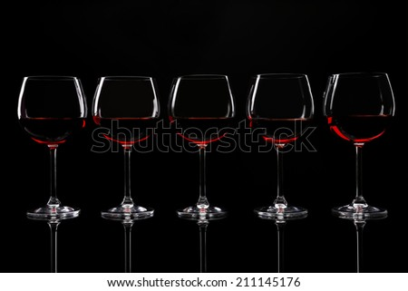 Glasses of wine isolated on black - stock photo