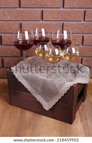 Glasses of wine on box on brick wall background - stock photo