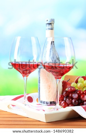 Glasses of wine on napkin on tray on wooden table on nature background