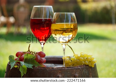 Glasses of wine on old barrel in a garden - stock photo