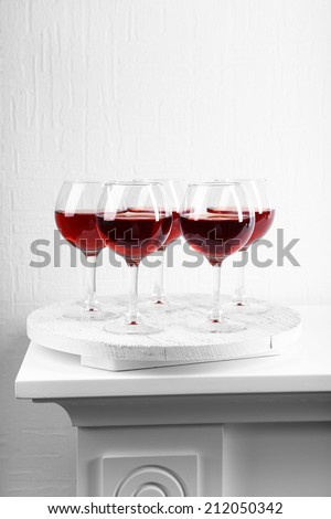 Glasses of wine on tray in room - stock photo