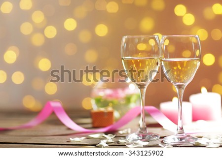 Glasses of wine, white roses and candles, on blurred background - stock photo