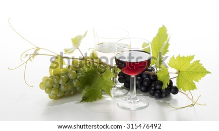 Glasses of wine with grapes on the white background