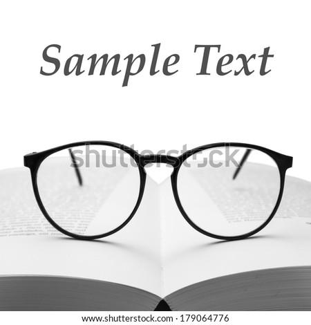 Glasses on a book isolated on white - stock photo