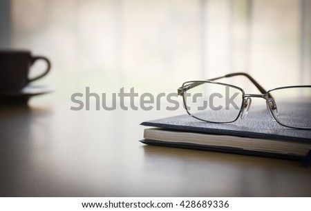 Glasses on a book with on the desk by nature light background - stock photo