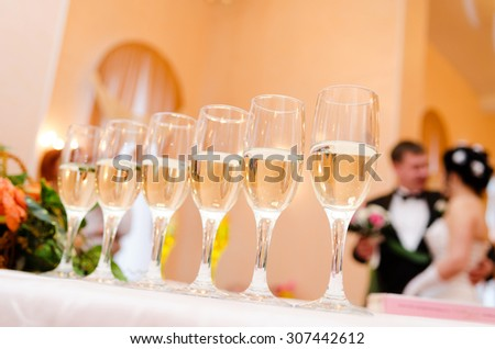 Glasses on background of the bride and groom - stock photo