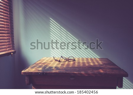 Glasses on desk by window with shadows from blinds - stock photo