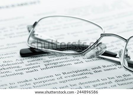Glasses on newspaper. Macro view - stock photo