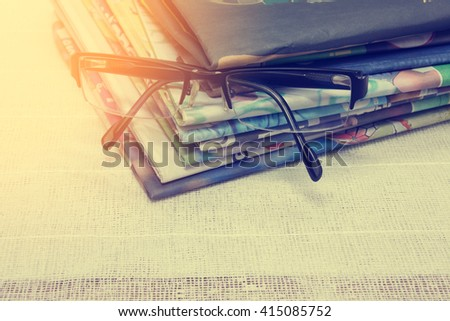 glasses on Newspapers stacked. - stock photo