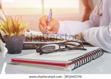 glasses on note book ,Doctor at work,  male doctor write prescription,medical record and computer on the table.,Doctor office table desk,and other things on wooden desk background.selective focus - stock photo