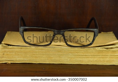 Glasses on old book on wood back ground. vintage in full length photo
