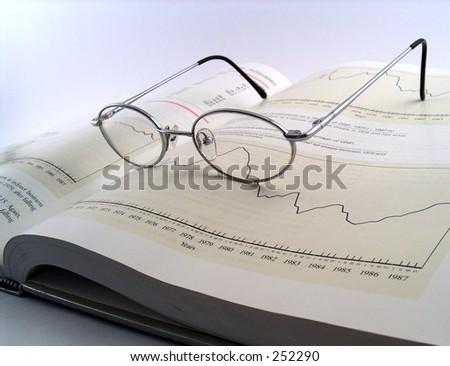 glasses on open finance book - stock photo