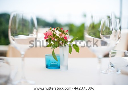 glasses on outdoor romantic table with flowers