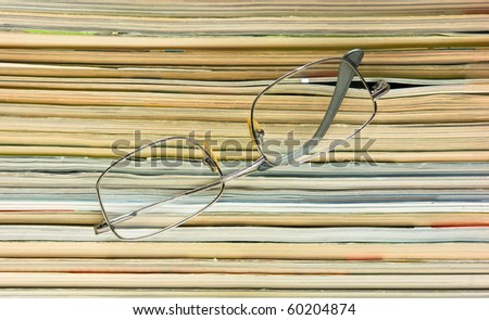 glasses  on the background of the stack of magazines - stock photo