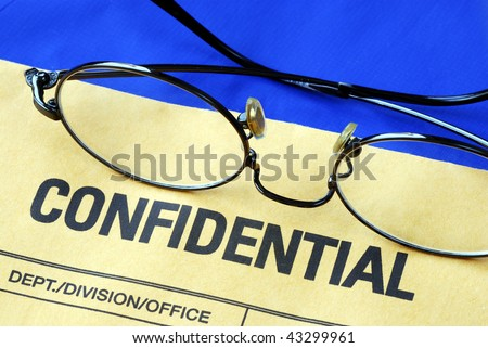 Glasses on the confidential envelope isolated on blue