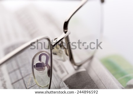Glasses on the newspapers closeup view - stock photo