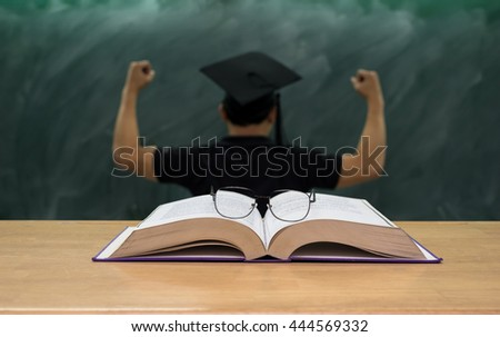 Glasses over the Books on the desk in class room with the man who wear the graduation cap over the black board background,Education concept - stock photo