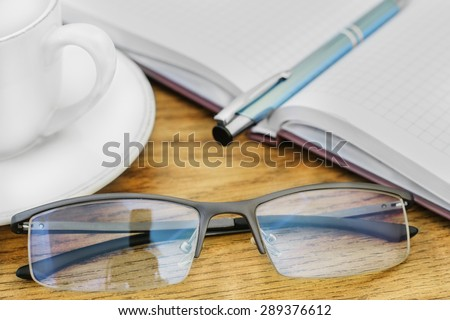 glasses pen on the table and pads